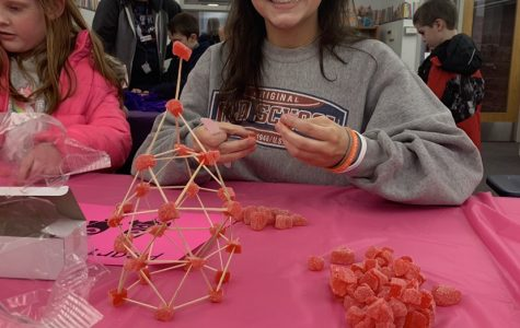 New member, Annie Mitchell, smiles for the camera during the Tri-c Elementary STEAM (Science, Technology, Engineering, Arts, and Mathematics) while working at the gummy rocket building station.
