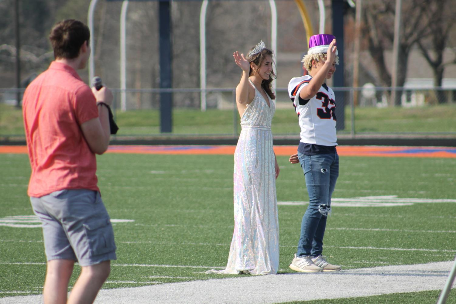 """Noah Adams (12) sings """"There She Is"""" by Frank Turner as Annabelle Barnstable and Jaxon Allen wave to the people in the stands."""